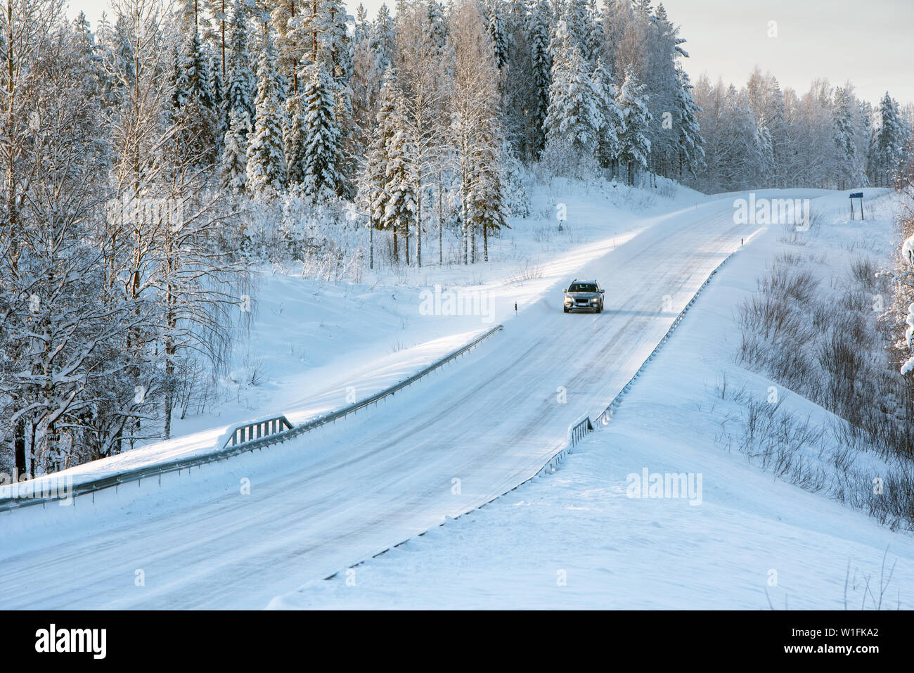 Snowy and icy road winding through winter forest landscape in Eastern Finland - Stock Image