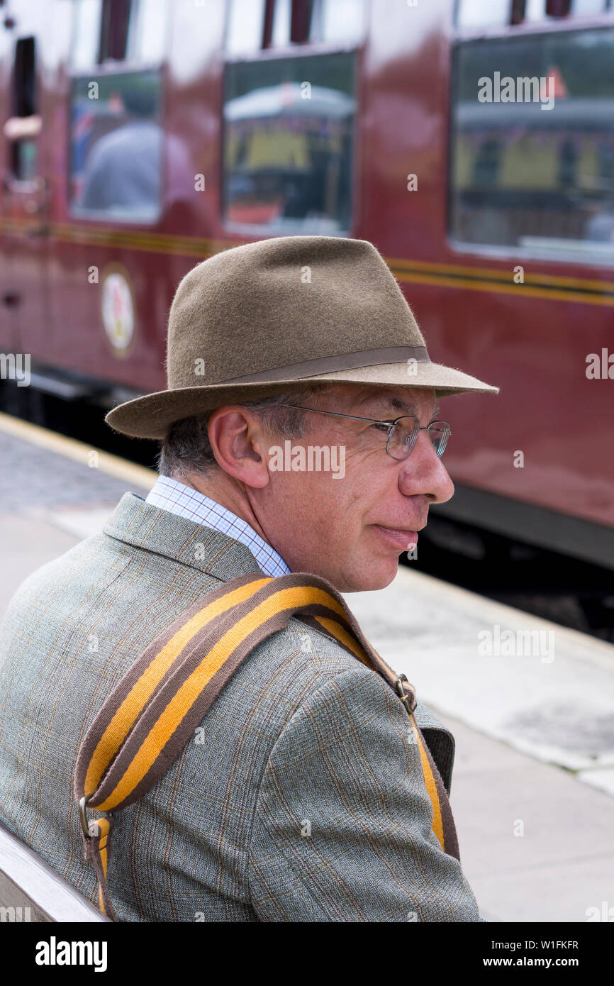 Kidderminster, UK. 29th June, 2019. Severn Valley Railways 'Step back to the 1940's' gets off to a fabulous start this weekend with costumed re-enactors playing their part in providing an authentic recreation of wartime Britain. Man in 1940s costume sits isolated on platform awaiting next steam train. Credit: Lee Hudson Stock Photo
