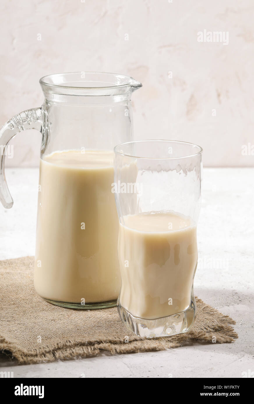 Close-up decanter and glass of oat milk on burlup napkin on white background. - Stock Image
