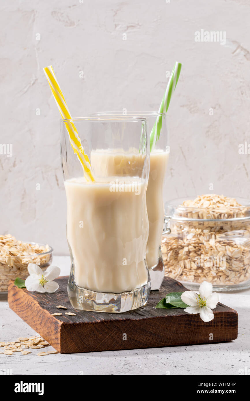 Two figured glasses with healthy oats milk on brown burned  board and jar of oaty flakes on light background. - Stock Image