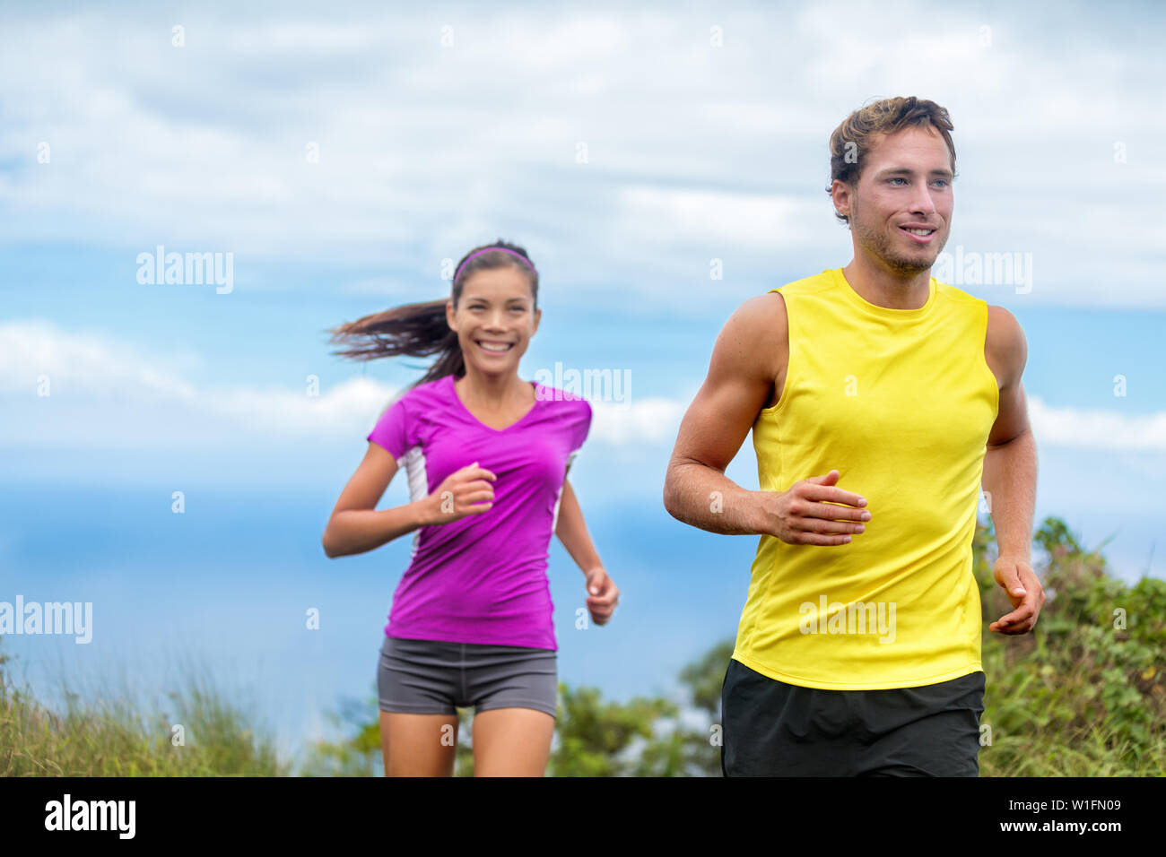 Healthy sports people trail running living an active life. Happy lifestyle couple of athletes training cardio together in summer outdoors. Multi-ethnic group Asian woman with handsome fit man trainer. - Stock Photo