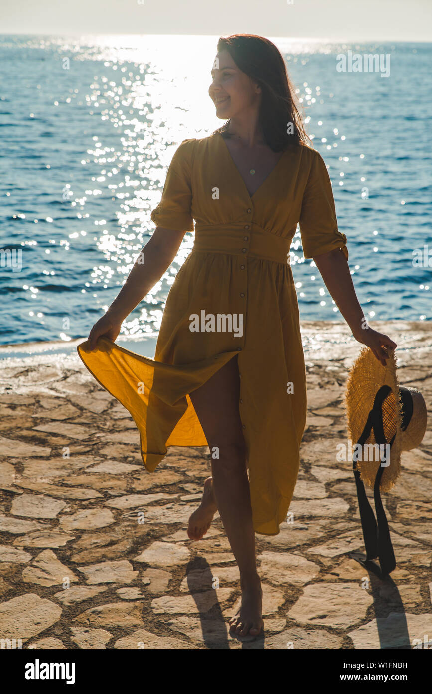 young pretty smiling woman in yellow sundress walking by stone beach. summer vacation concept - Stock Image