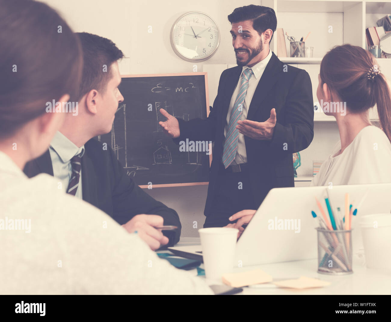 Confident businessman discussing new business project with members of his team - Stock Image