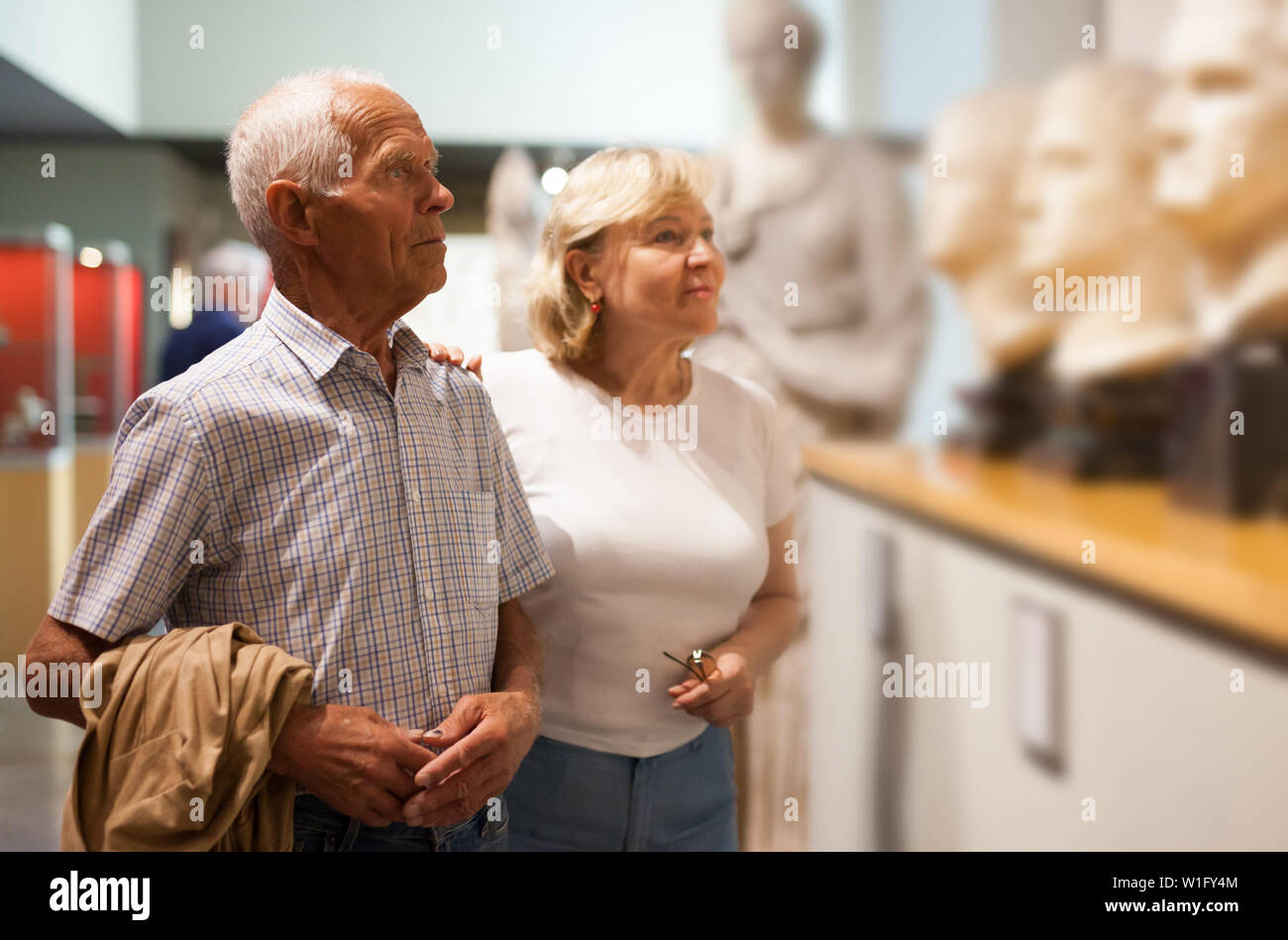 Positive elderly couple looking at exhibits on exposition of museum - Stock Image