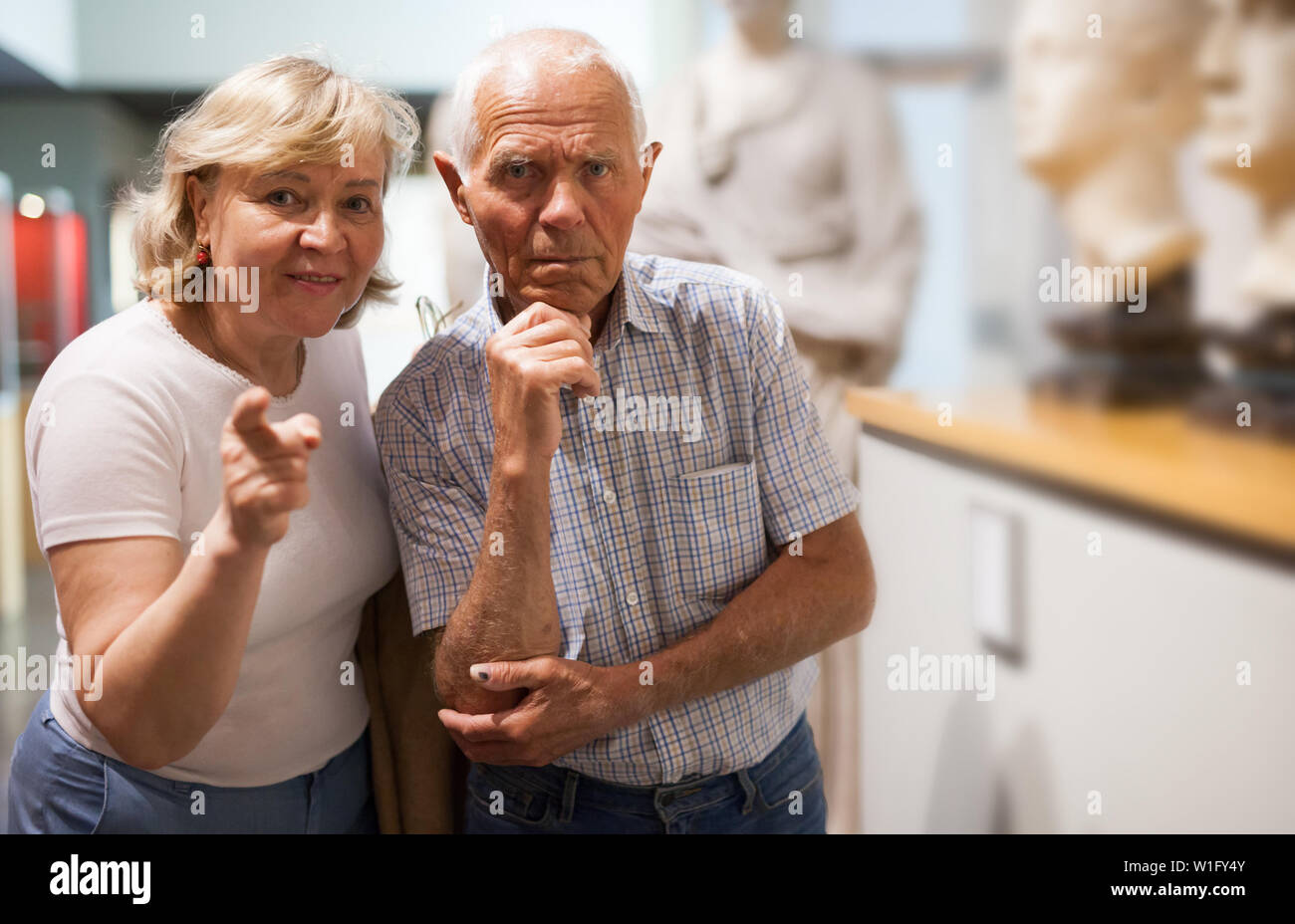 Positive couple of pensioners standing at hall of museum and looking at exhibits - Stock Image