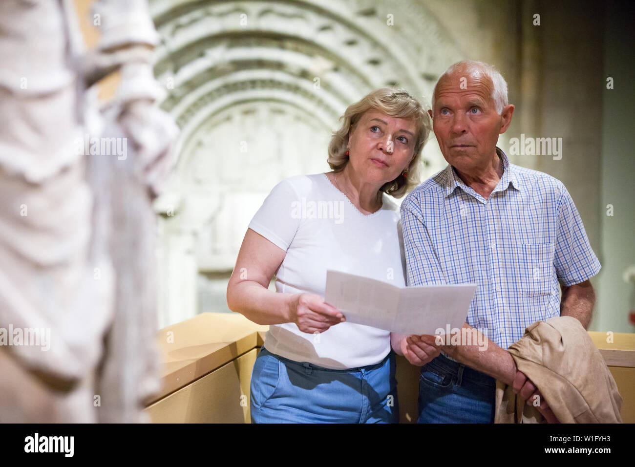 Positive elderly man and woman with guidebook standing at hall of Art Museum - Stock Image
