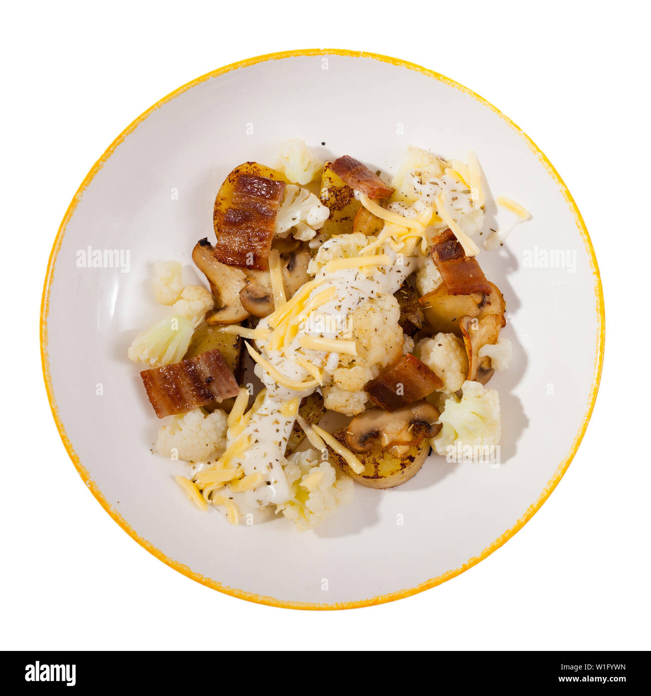 Top view of baked potatoes served with cauliflower, bacon and mushrooms with sauce and grated cheese on white plate. Isolated over white background - Stock Image