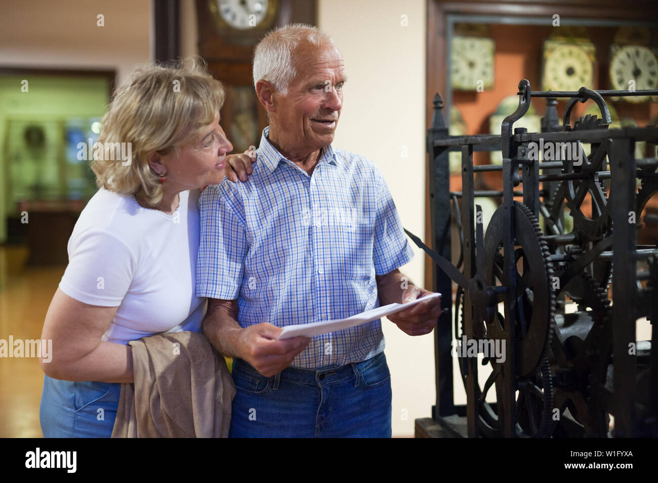 Male and female pensioners visiting exposition of museum and reading guidebook - Stock Image