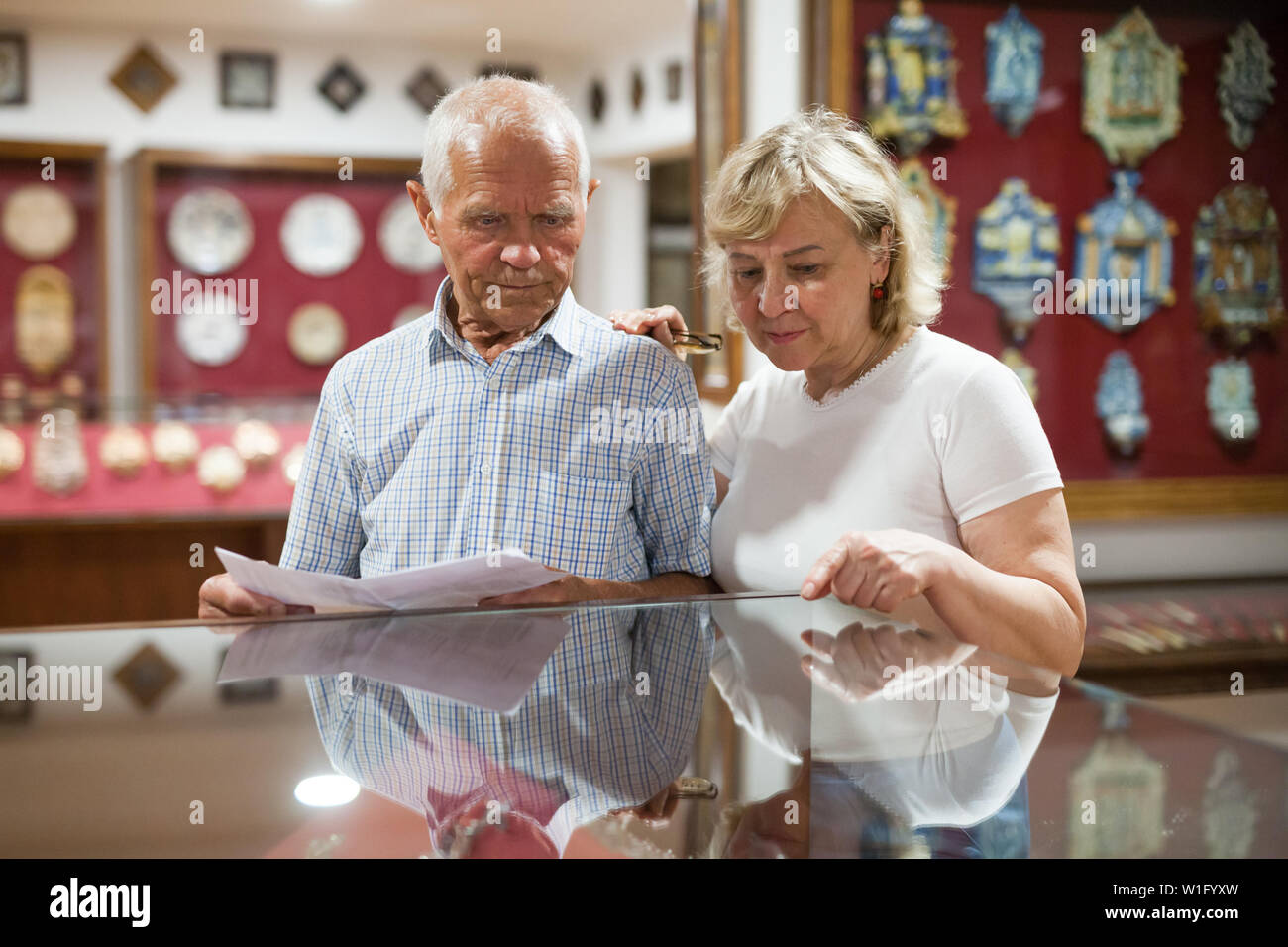 Mature male and female looking at exhibits In glass stands in historical museum - Stock Image
