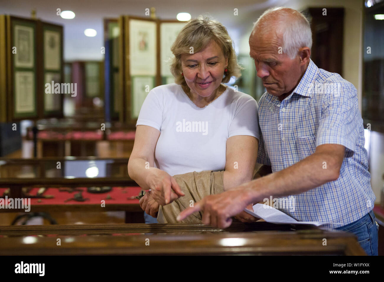 Senior couple looking at stands with exhibits in historical museum hall - Stock Image