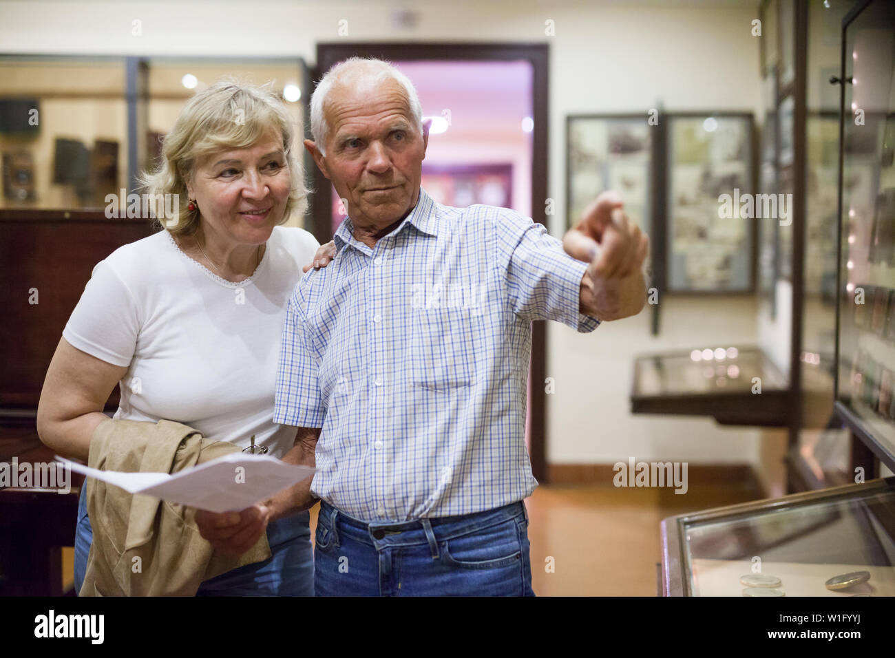 Senior couple holding brochure with information about exhibits on exposition of museum - Stock Image