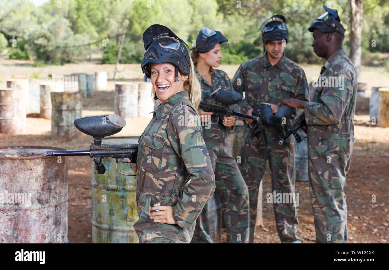 Portrait of happy female paintball player with marker gun ready for game outdoors Stock Photo
