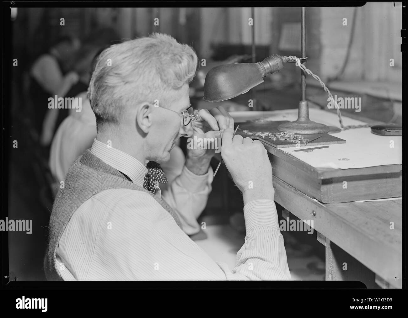 Lancaster, Pennsylvania - Hamilton Watch. Operation - inspecting plate - skilled inspecting job (all plates must undergo severe inspection covering all operations of drilling, tapping, recessing, and facing.) - Stock Image
