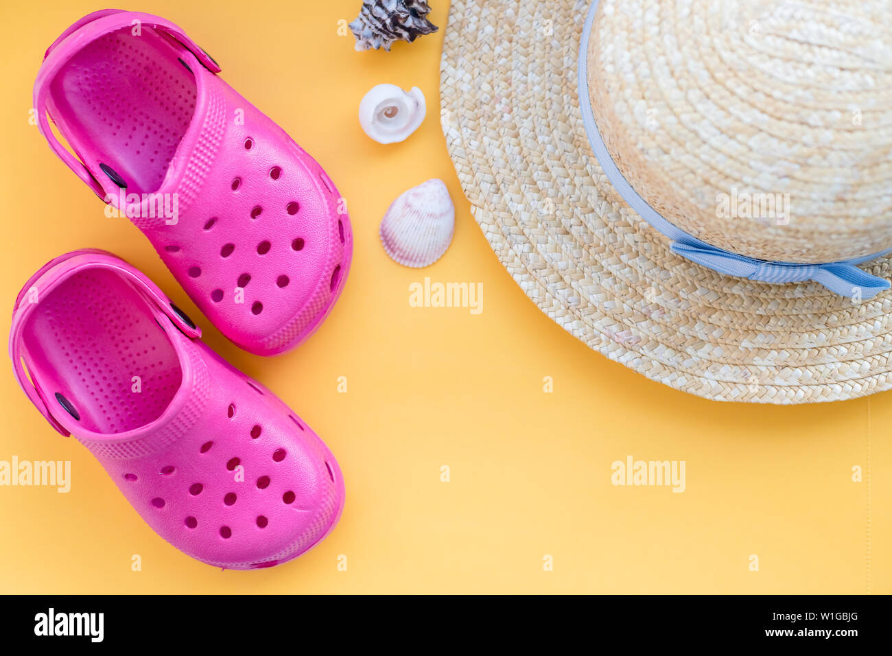 San Diego, USA,May 10, 2019. Flat lay composition with beach shoes, hat, seashells and space for text on yellow background.sandals with seashell - Stock Image