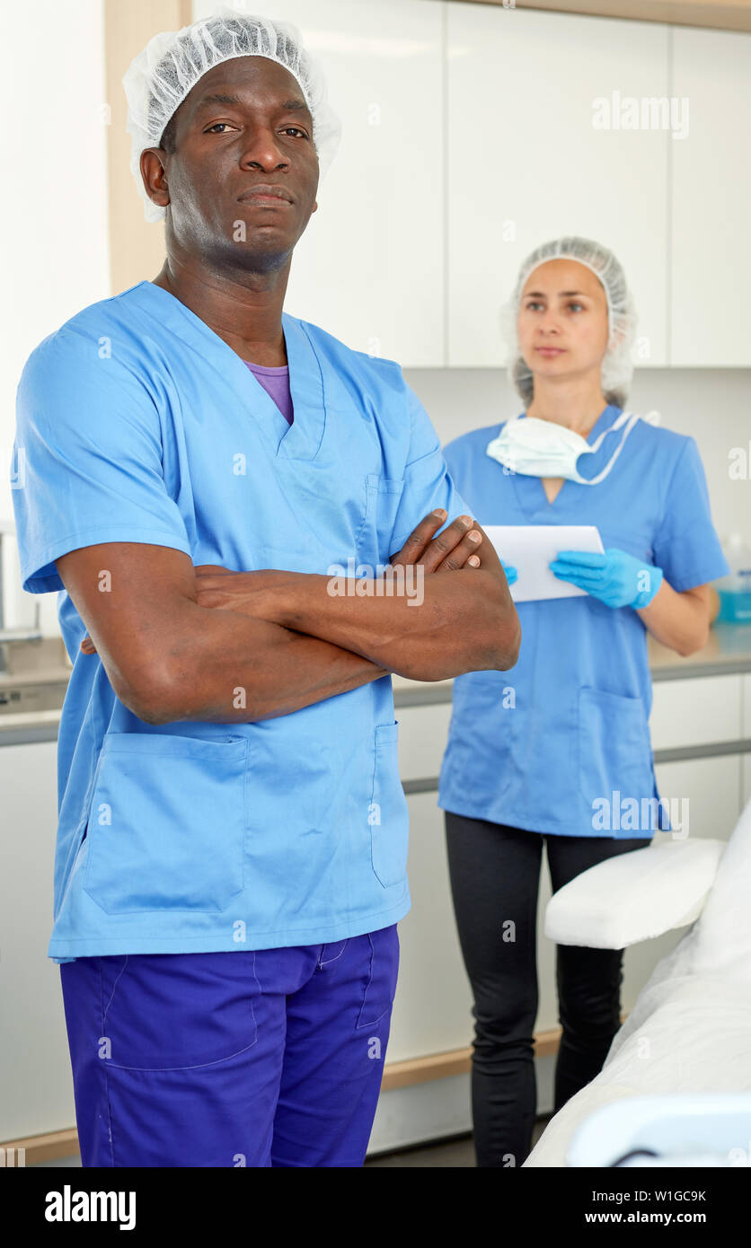 Cosmetician man before procedure in clinic of esthetic cosmetology, woman on background - Stock Image