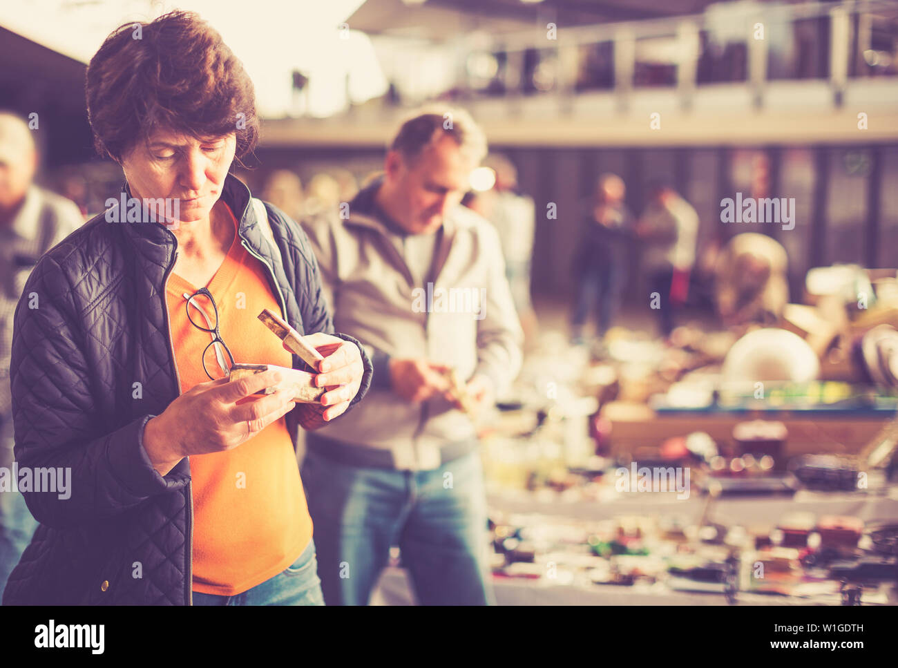 Mature female is visiting the market of old things and choosing casket outdoors - Stock Image