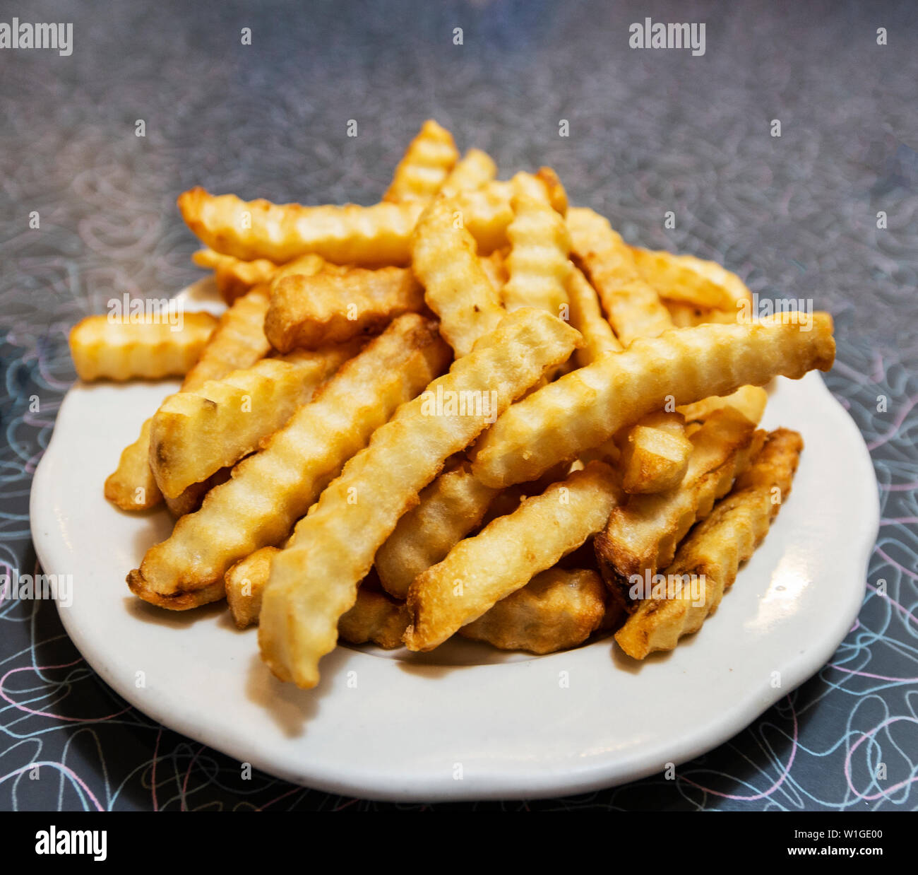 A white plate with golden thick cut french fries on a dinner table. - Stock Image