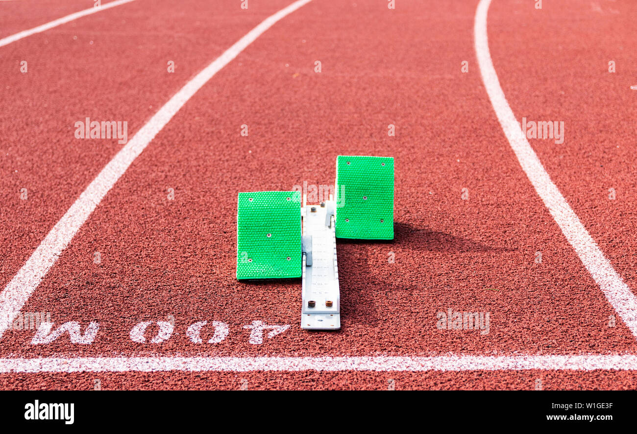 A set of green blocks are ready to be used in a race set up on at the 400 meter start line on a red track. - Stock Image