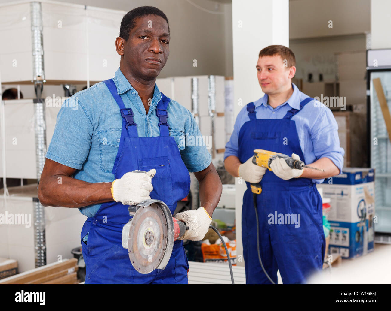 Confident African-American builder holding manual disc grinder, working with workmate at renovation indoors - Stock Image