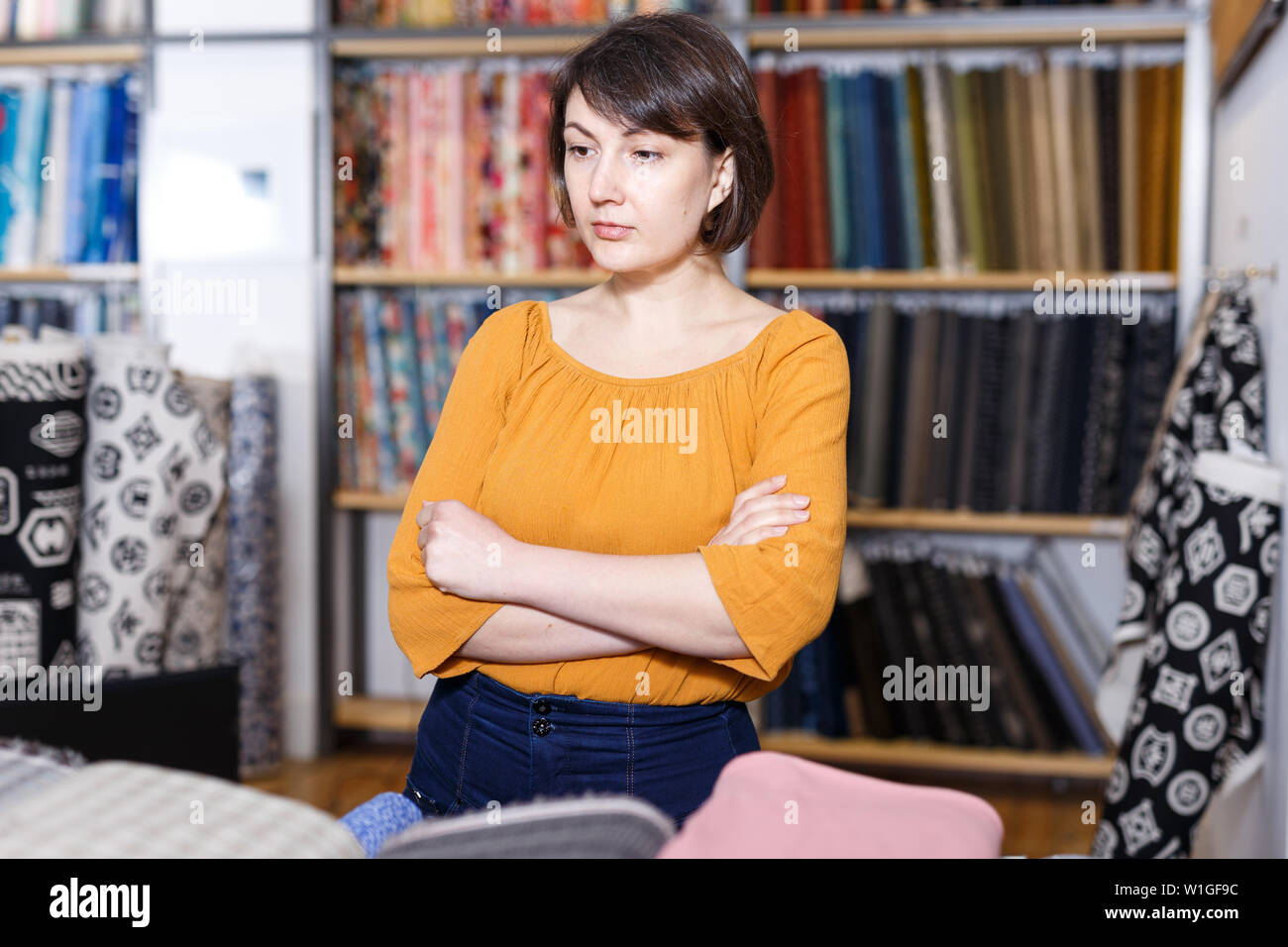 Thoughtful woman standing near shelves with colorful fabrics in shop, choosing materials for dressmaking - Stock Image