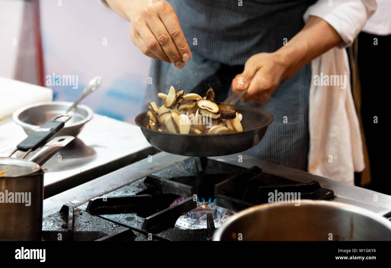 chef frying mushrooms in the kitchen of the restaurant - Stock Image