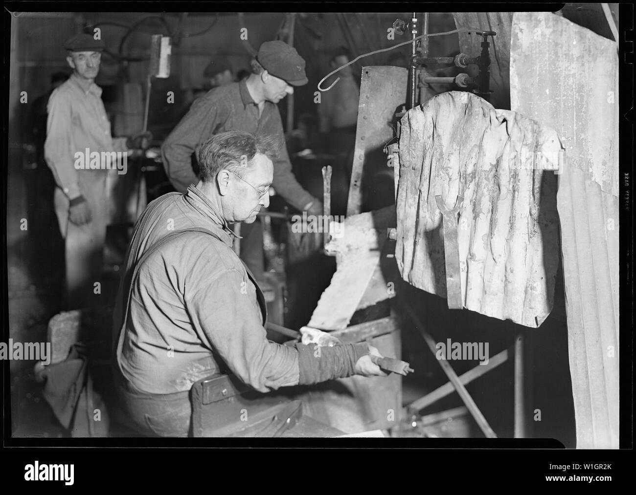 Millville, New Jersey - Glass bottles. T. C. Wheaton gaffer finishing necks of wide mouthed jars. He rotates the bottle on a sheet of iron pressing open the mouth with the tool he is holding in his right hand. The jars are then taken by snapping-up boy to be annealed. The white formation on the right hand side of the picture is molten glass which has been hung there by the blowers. It is the excess glass which has been left over after they finished blowing the bottle. Stock Photo