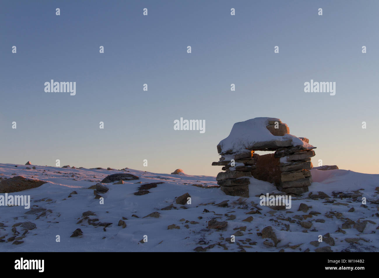 Inuksuk (or spelled Inukshuk) Inuit landmark covered in snow  at sunrise found on a hill near the community of Cambridge Bay, Nunavut, Canada - Stock Image