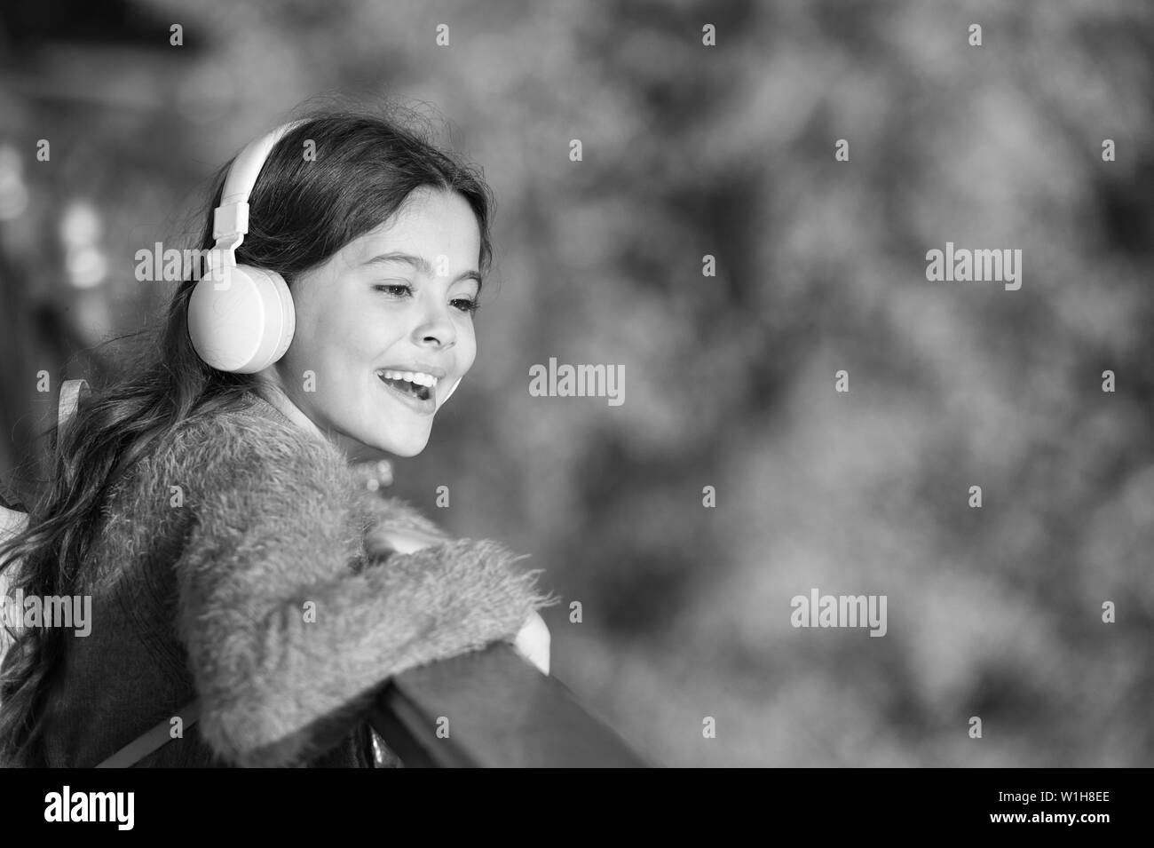 Get happy yourself. Girl modern headphones enjoy relax. Look on bright side. Secrets to raising happy child. Girl cute kid green grass background. Healthy emotional happy kid relaxing outdoors. - Stock Image