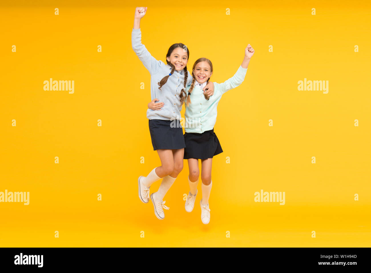 Kids cute students. Schoolgirls best friends excellent pupils. Schoolgirls tidy appearance school uniform. School friendship. September again. Childhood happiness. School day fun cheerful moments. Stock Photo