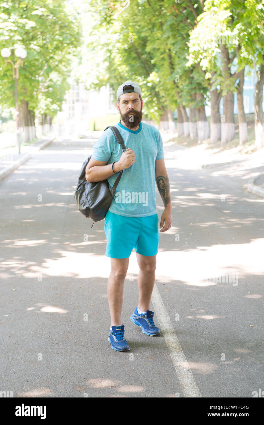 Handsome athlete. Sport coach with backpack ready for workout outdoors. Sport is way of life. Guy handsome bearded face in sport uniform in park. Summer workout. Daily walk to gym. Health care. - Stock Image