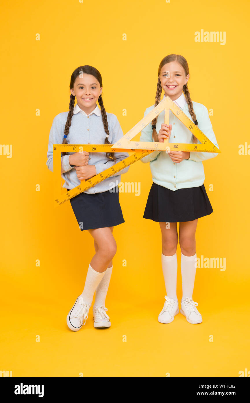 Move from theory to practice. Excellent pupils. Secondary school. Schoolgirls tidy appearance school uniform hold big rulers for geometry school lesson. Kids cute students study math. Knowledge day. - Stock Image