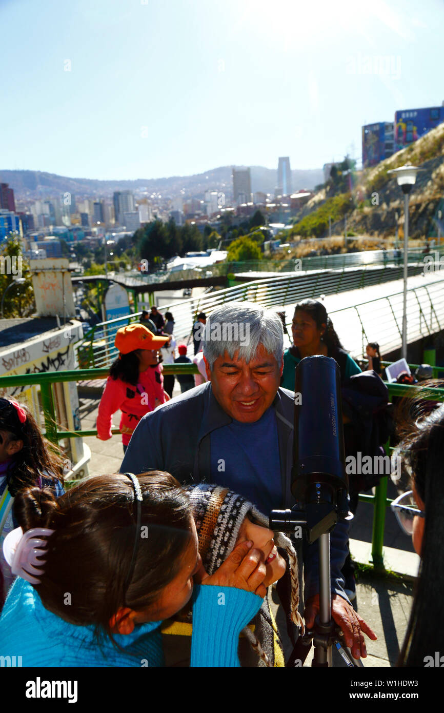 La Paz, Bolivia 2nd July 2019: An Aymara boy observes a partial eclipse of the sun through a telescope at an eclipse watching event near the city centre. In La Paz the eclipse lasted for about 2 hours 10 minutes with about 55% coverage at its maximum. The skyscraper right of centre is the new Presidential Palace / Casa Grande del Pueblo. Stock Photo