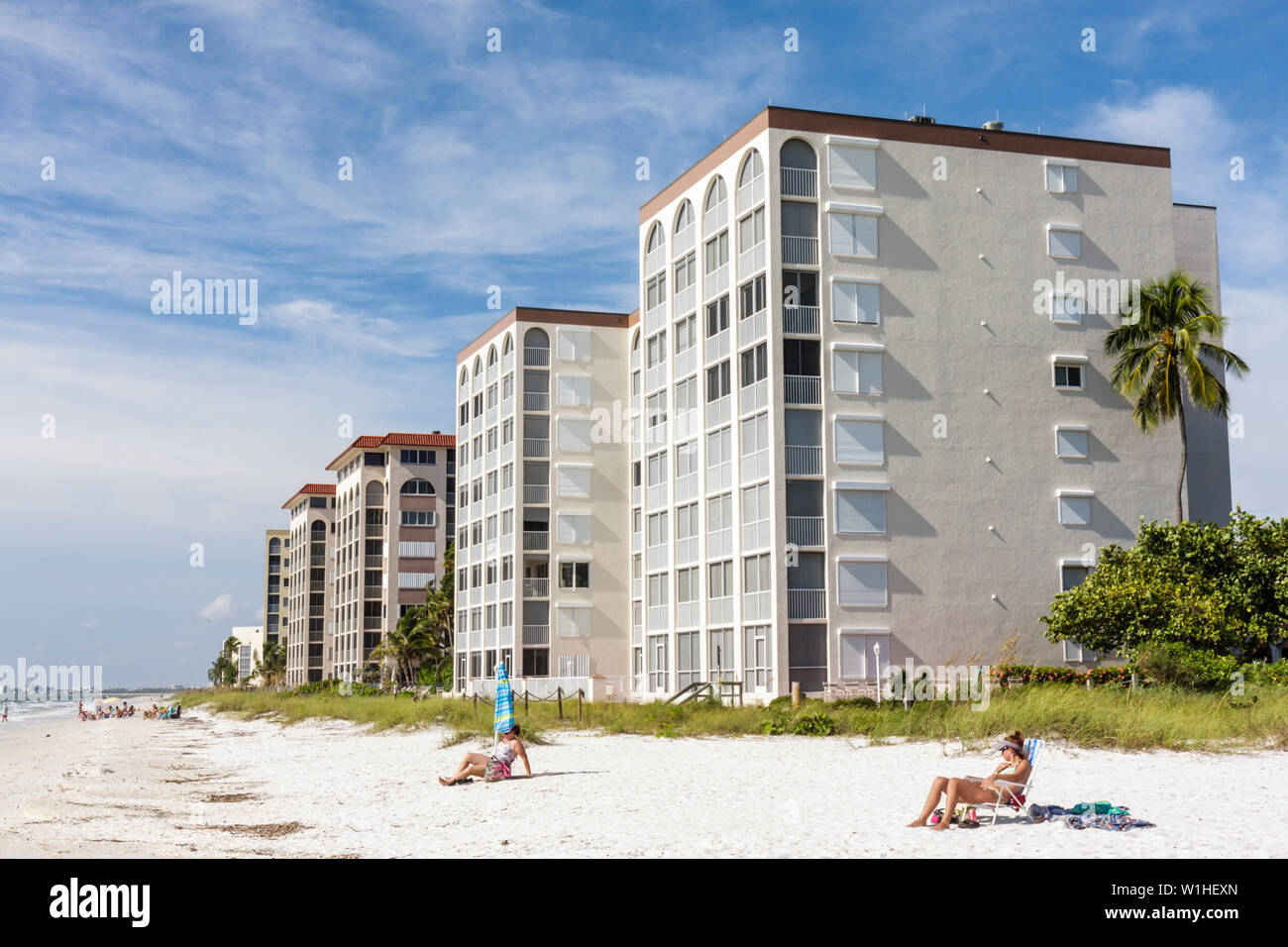 Florida Bonita Springs Gulf of Mexico public beach Little Hickory Beach oceanfront condominium building prime real estate woman - Stock Image