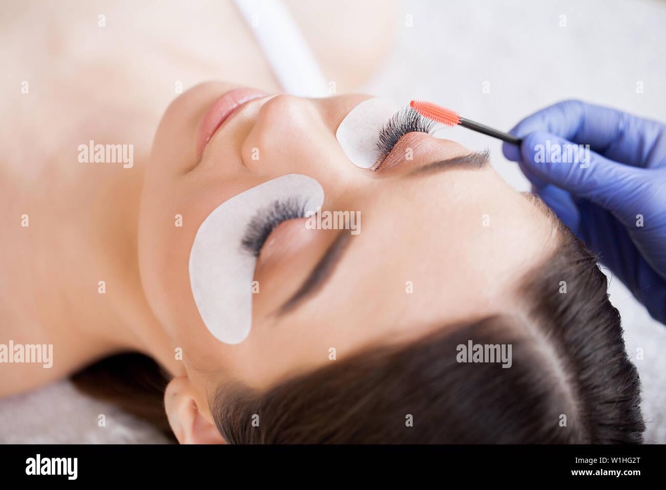 2b1b01290d5 Eyelashes extensions. Fake Eyelashes. Eyelash Extension Procedure.  Professional stylist lengthening female lashes.