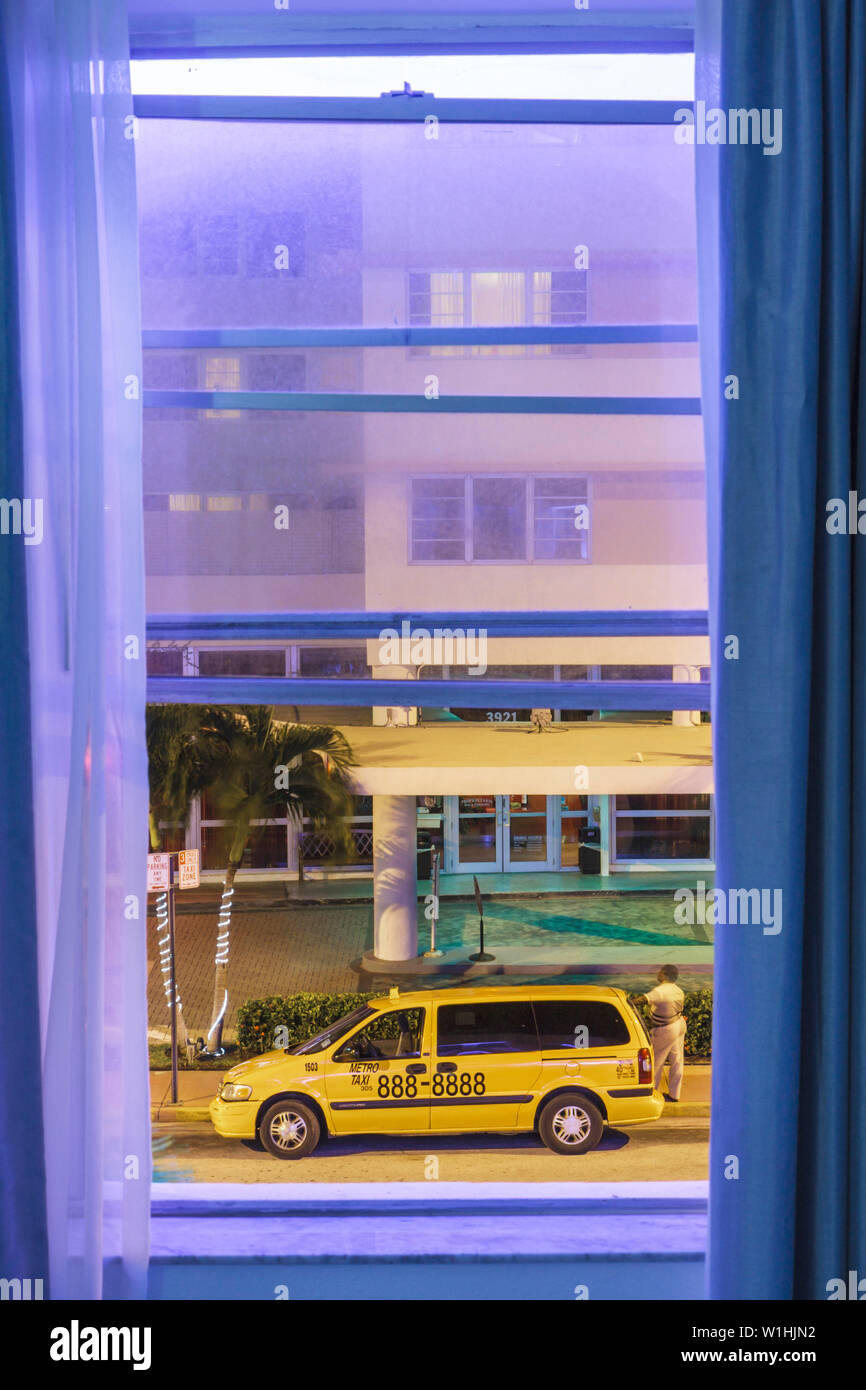 Miami Beach Florida Collins Avenue Circa 39 Hotel room window view night street taxi taxicab stand blue neon driver - Stock Image