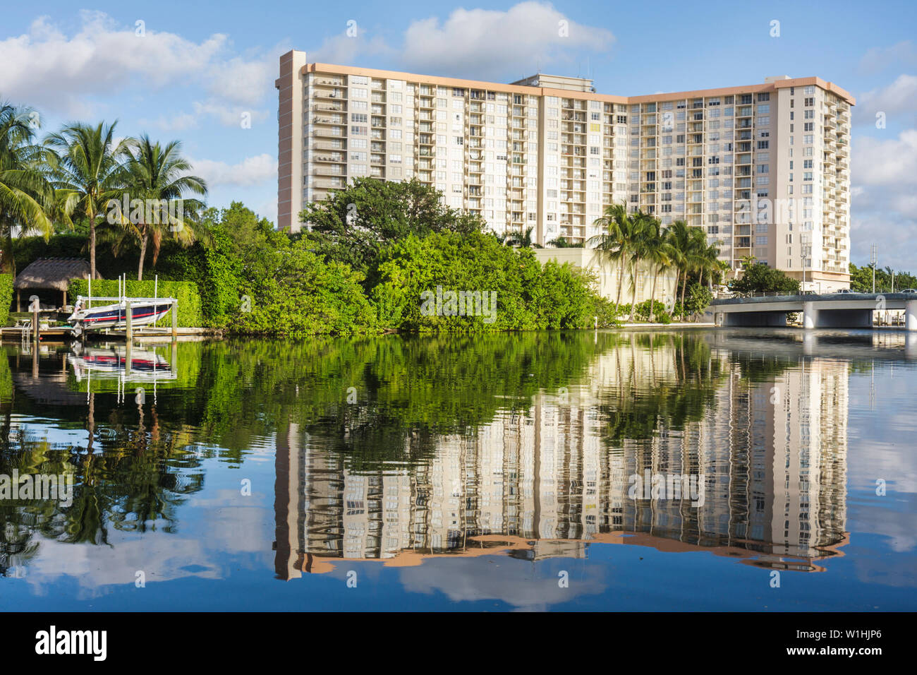 Miami Beach Florida 41st Street Bridge Indian Creek waterway high-rise building condominium water reflection shore dry-dock boat - Stock Image