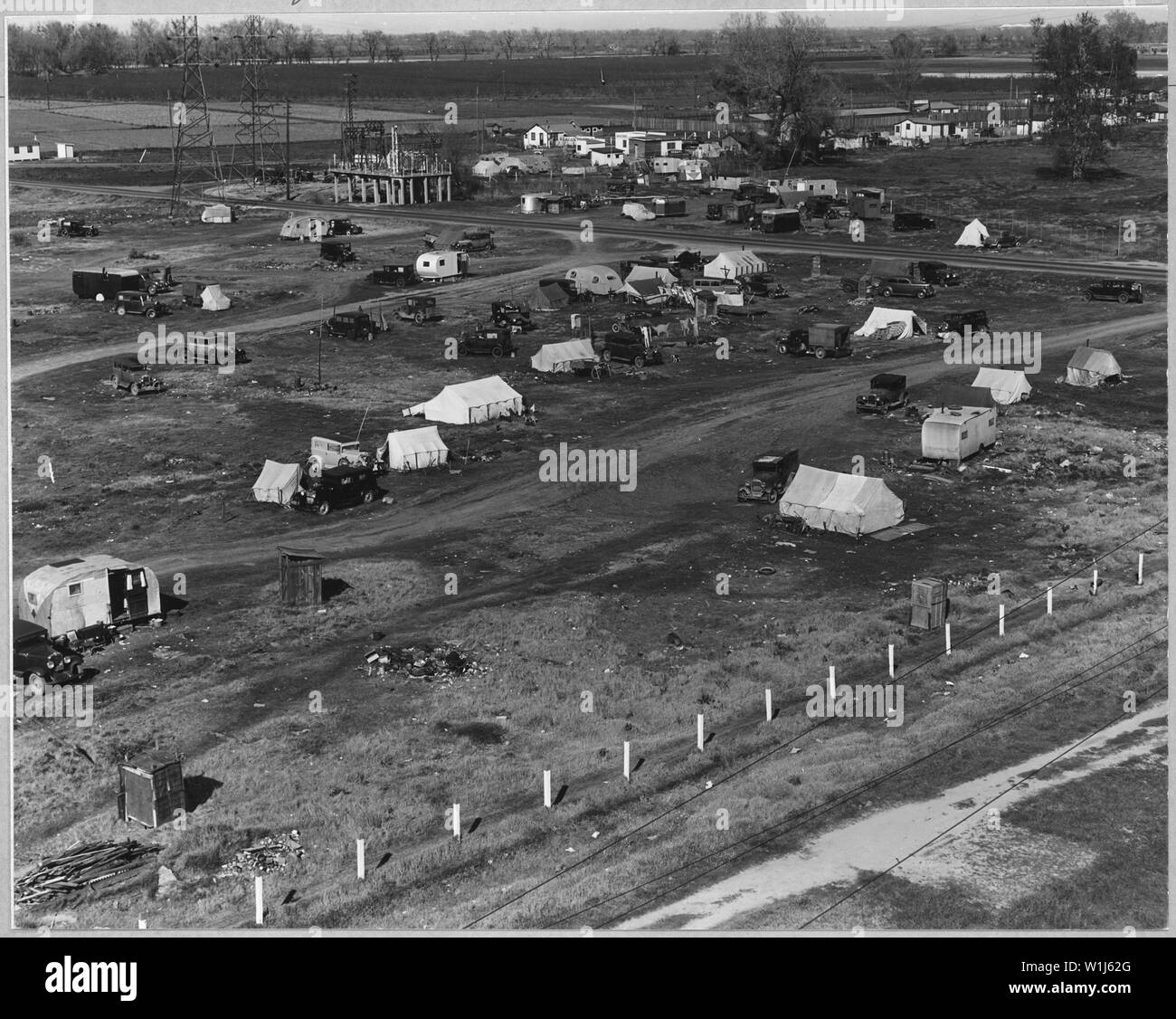 Sacramento, California. Squatter camp of agricultural labor migrants one-eighth mile outside city li . . .; Scope and content:  Full caption reads as follows: Sacramento, California. Squatter camp of agricultural labor migrants one-eighth mile outside city limits of state capital of California. Above 125 units mostly families without sanitation water donated by power company from single faucet. Across main road (upper right of picture) is a trailer camp. Beyond is a newly developing shacktown community where lots are being sold and families are settling in makeshift home-built cabins and cotta - Stock Image
