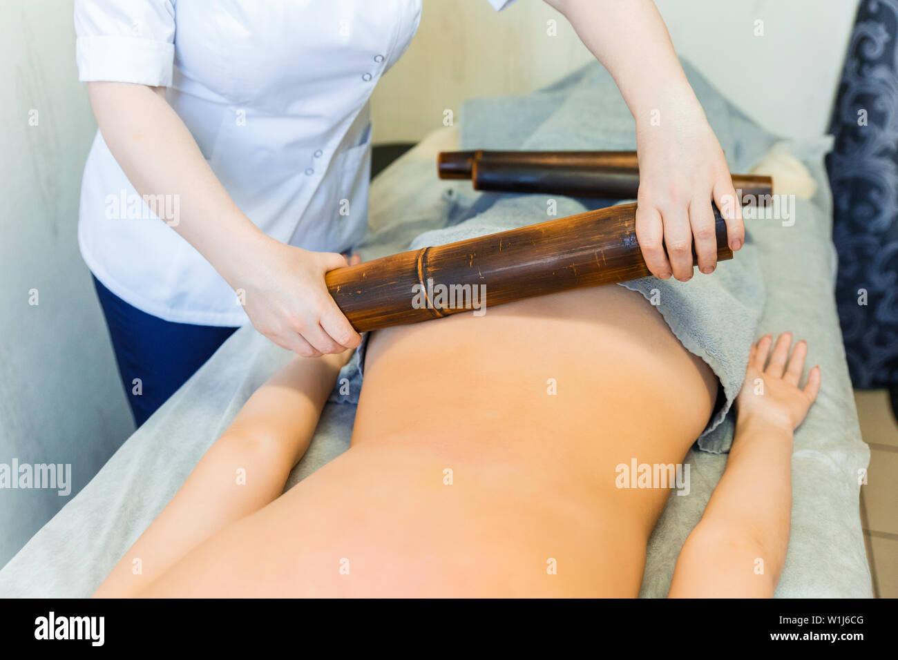Back massage with bamboo sticks. Bamboo massage sticks. - Stock Image
