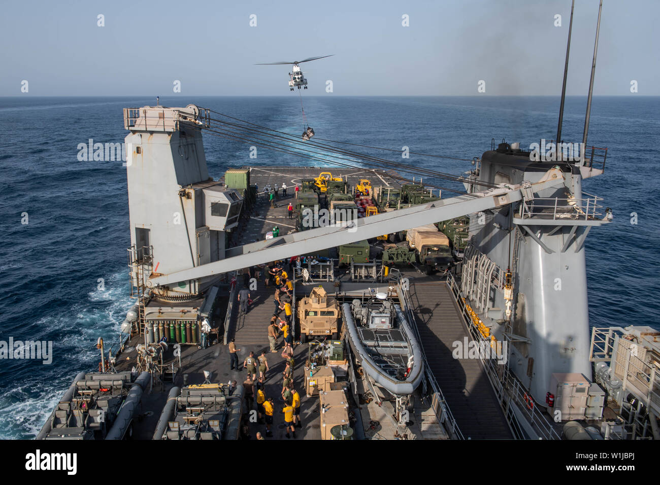 190630-N-HD110-0320  GULF OF ADEN (June 30, 2019) An SA-330J Puma helicopter, attached to the Military Sealift Command dry cargo and ammunition ship USNS Cesar Chavez (T-AKE 14), delivers cargo to the flight deck of the amphibious dock landing ship USS Harpers Ferry (LSD 49) during a vertical replenishment. Harpers Ferry is part of the Boxer Amphibious Ready Group and 11th Marine Expeditionary Unit and is deployed to the U.S. 5th Fleet area of operations in support of naval operations to ensure maritime stability and security in the Central Region, connecting the Mediterranean and the Pacific - Stock Image