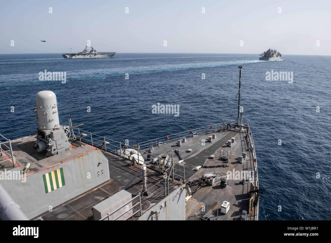 190630-N-HD110-0259  GULF OF ADEN (June 30, 2019) The amphibious dock landing ship USS Harpers Ferry (LSD 49) transits alongside the amphibious assault ship USS Boxer (LHD 4), left, while it completes a vertical replenishment with the Military Sealift Command dry cargo and ammunition ship USNS Cesar Chavez (T-AKE 14). Harpers Ferry is part of the Boxer Amphibious Ready Group and 11th Marine Expeditionary Unit and is deployed to the U.S. 5th Fleet area of operations in support of naval operations to ensure maritime stability and security in the Central Region, connecting the Mediterranean and t - Stock Image