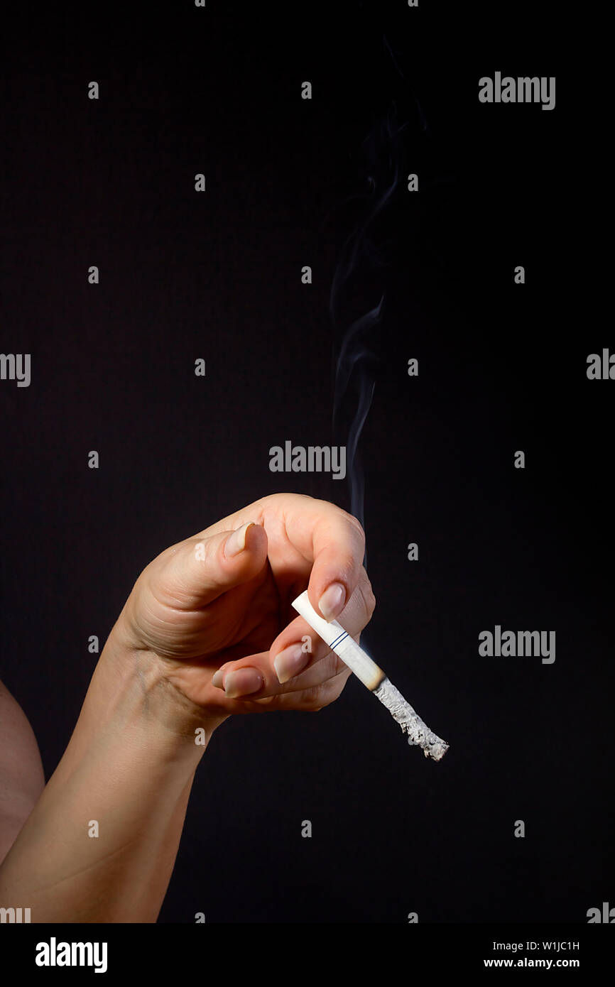Female hand holding a smoldering cigarette on a black background - Stock Image