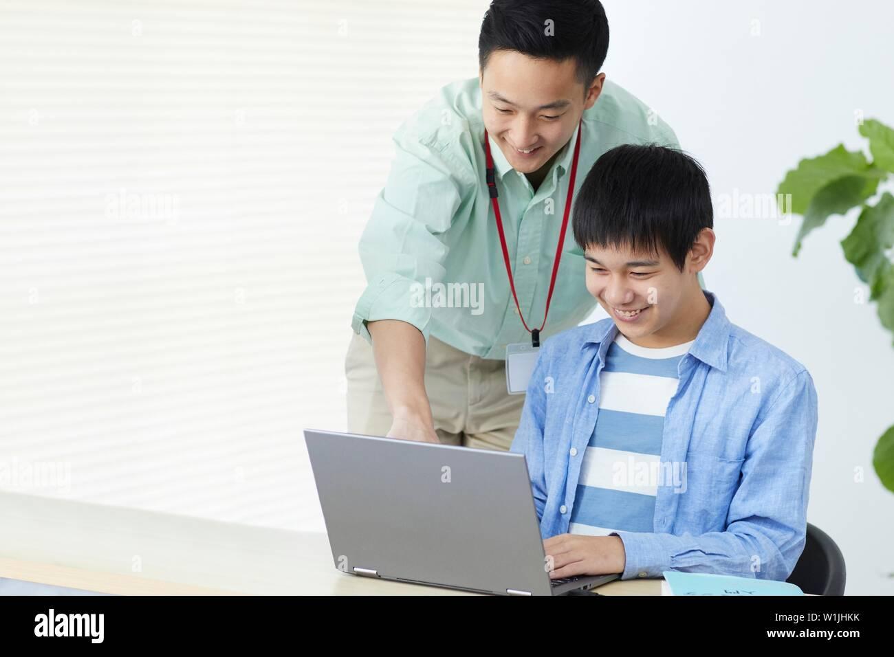 Japanese teenager studying programming - Stock Image