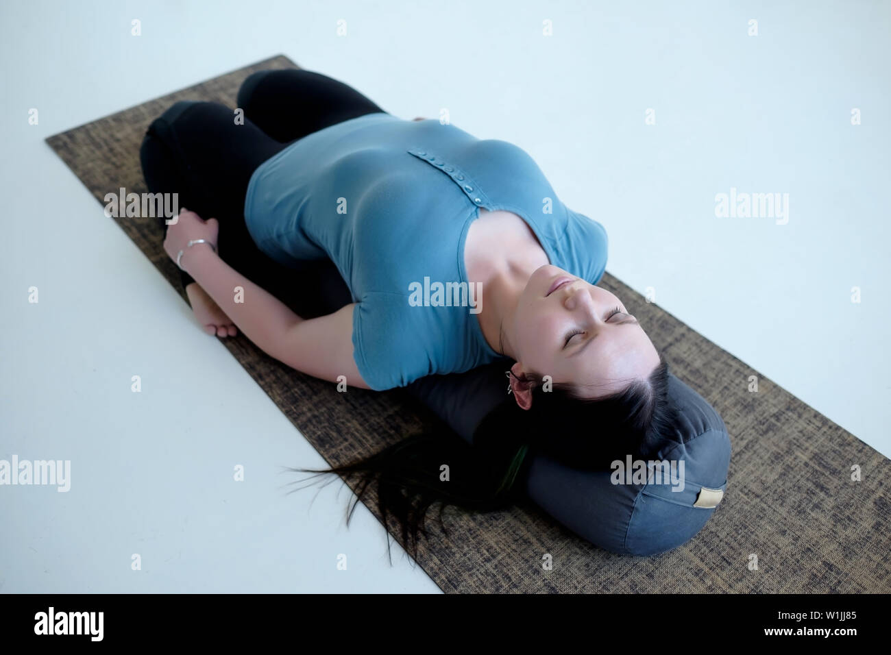 Cauacasian woman resting in reclining hero pose or Supta Virasana with bolster, stretching after practice. Studio shot - Stock Image