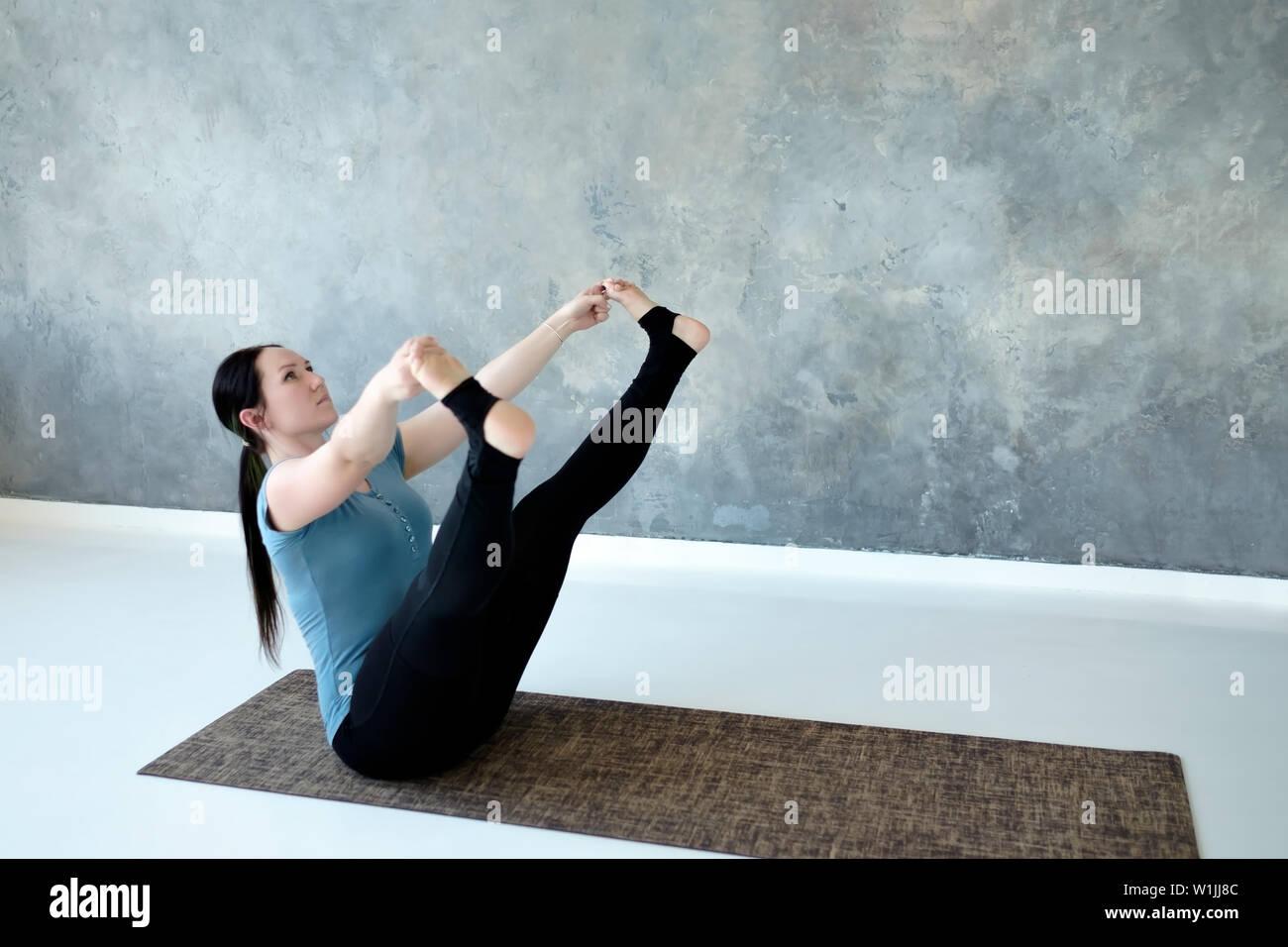 Young woman practicing yoga, doing wide legged boat exercise, Prasarita Navasana - Stock Image