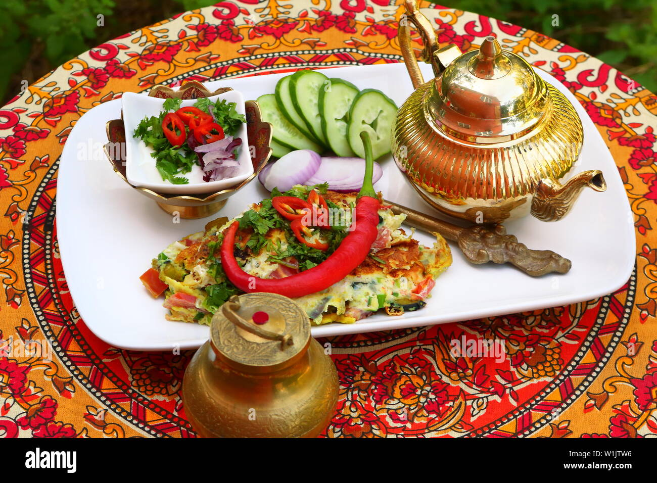 Indian omelet with vegetables and white sauce with tea on a beautiful red tablecloth with ornament - Stock Image