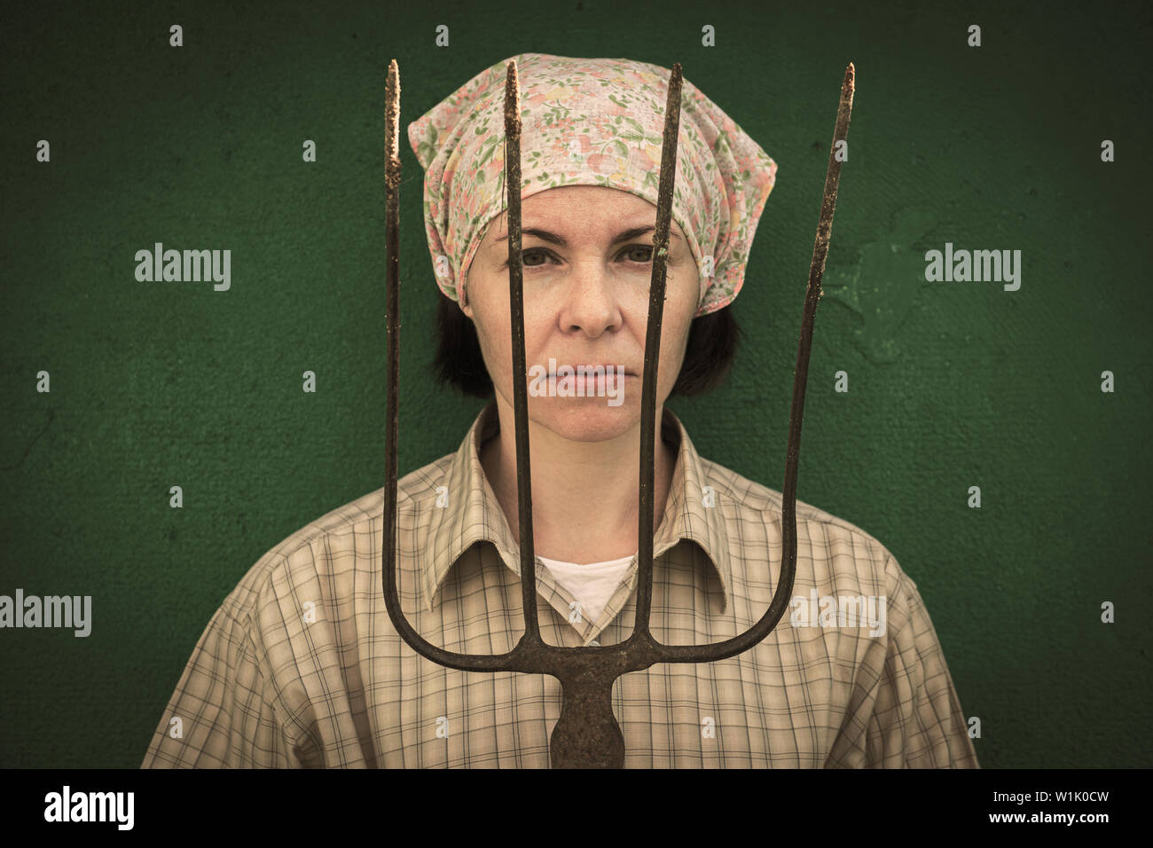 Young woman stands with a pitchfork near a stable on a ranch Stock Photo