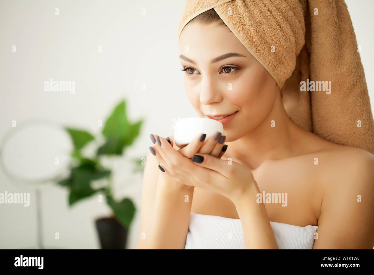 Young Spa Model with Clear Skin and Towel. Beautiful Spa Woman Applyng Monsturizing Cream. Skincare, Bodycare and Spa Beauty Concept - Stock Image