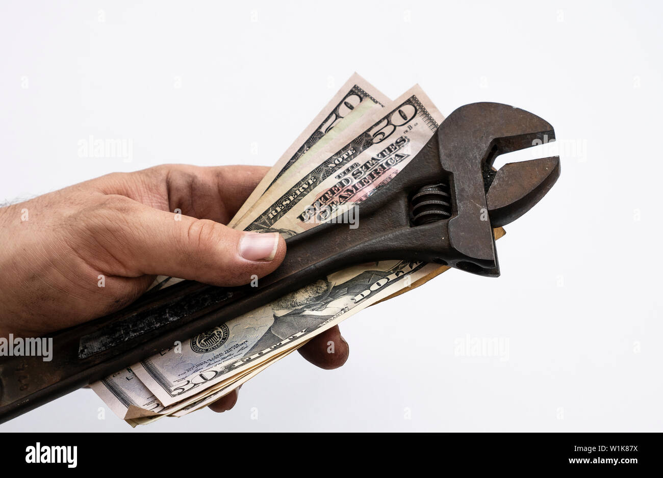 Technician with dirty hands holding wrench and USD bills in his hand Isolate over white background - Stock Image