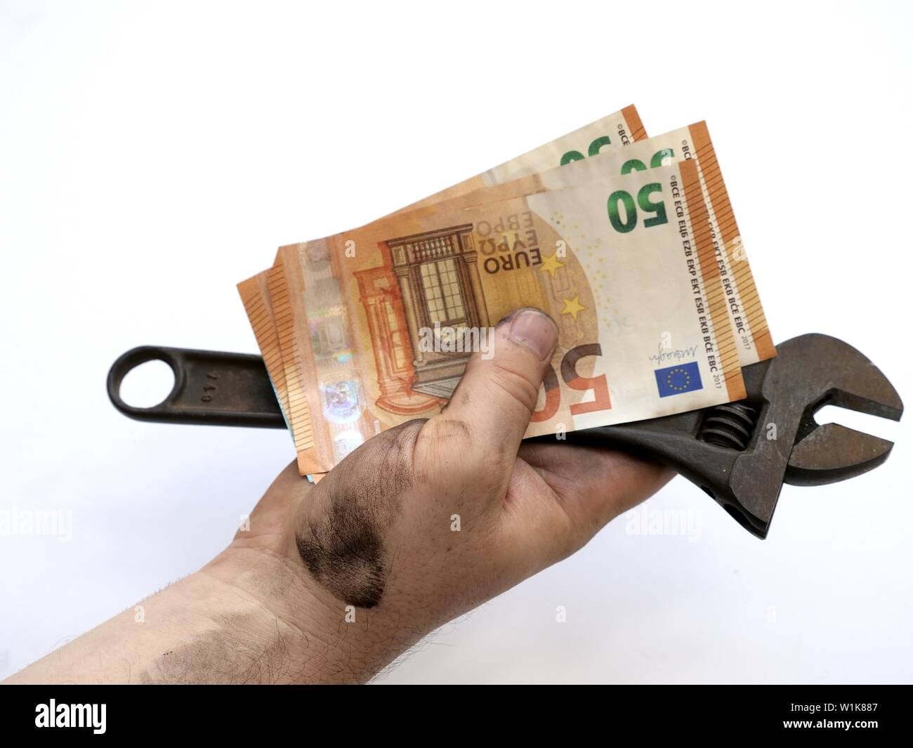 Technician with dirty hands holding wrench and Euro bills in his. Isolated on white. - Stock Image