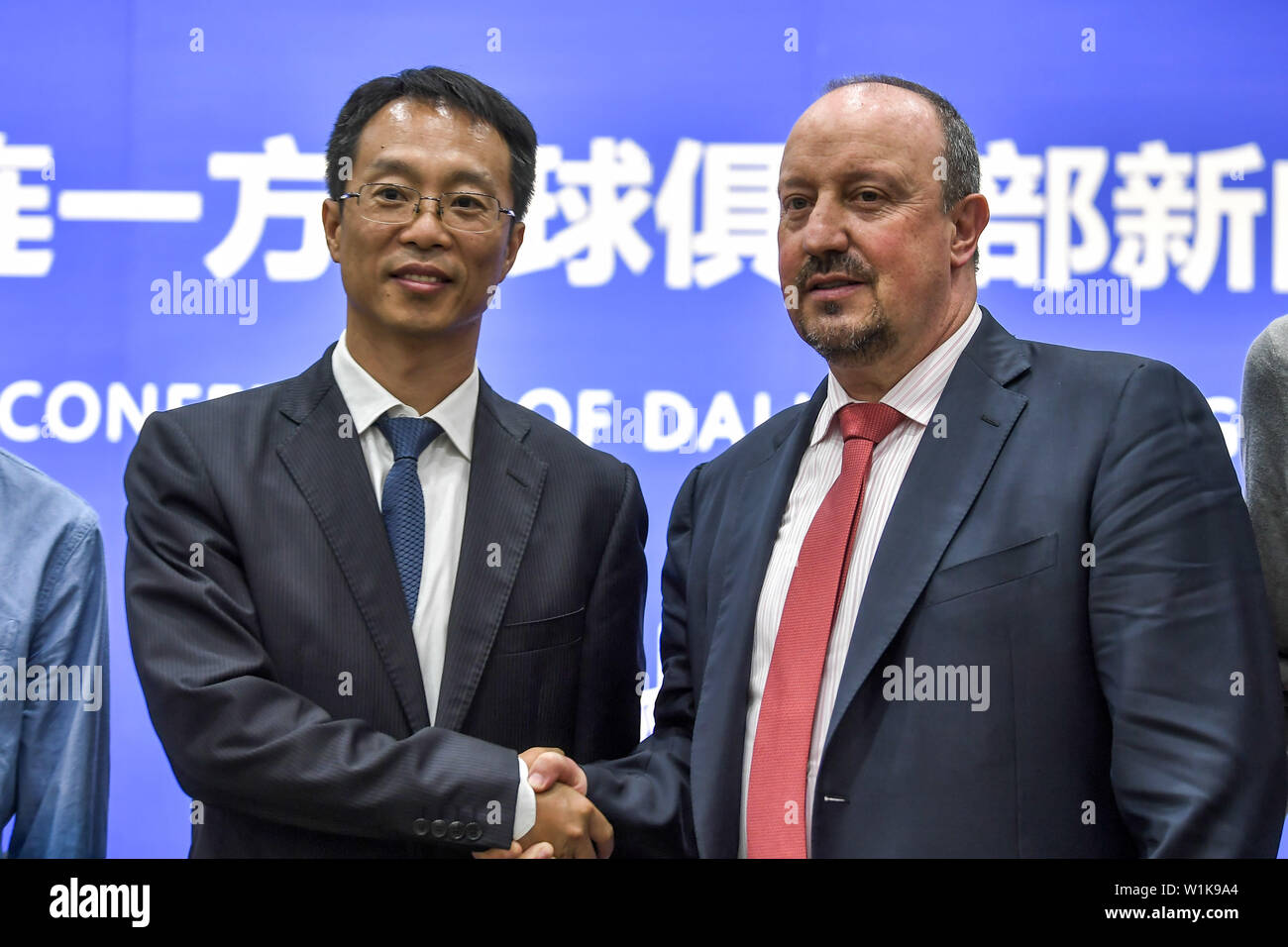 Spanish football manager Rafa Benitez, right, the new-appointed head coach of China's Dalian Yifang F.C., shakes hands with Zhang Lin, Chairman of Dalian Yifang F.C., during a press conference in Dalian city, northeast China's Liaoning province, 2 July 2019. Former Newcastle United manager Rafa Benitez is reportedly set to move to China to take charge of Chinese Super League side Dalian Yifang, after the departure of Choi Kang-hee. Sky Sports reported that the 59-year-old Spaniard has agreed a contract with Dalian which doubles the six million pounds a year he earned at St James's Park, and wi - Stock Image